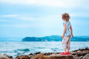 happy child girl relaxing on stone beach, traveling in Europe on summer vacations